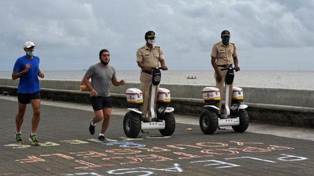 Police officers patrol on Segways as men wearing protective face masks run along the promenade at Marine Drive, after authorities eased lockdown restrictions that were imposed to slow the spread of the coronavirus disease (Covid-19), in Mumbai.(REUTERS)