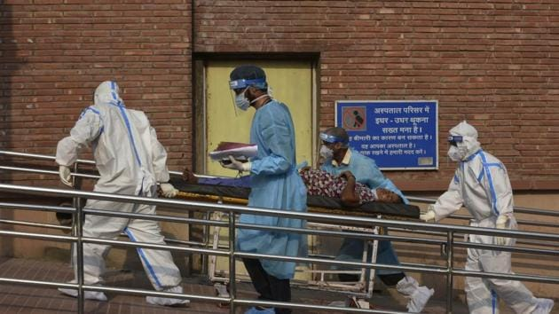 Medical professionals wearing PPE coveralls escort a patient suspected of coronavirus infection into the the Covid-19 ward at LNJP Hospital in New Delhi.(Vipin Kumar/HT PHOTO)