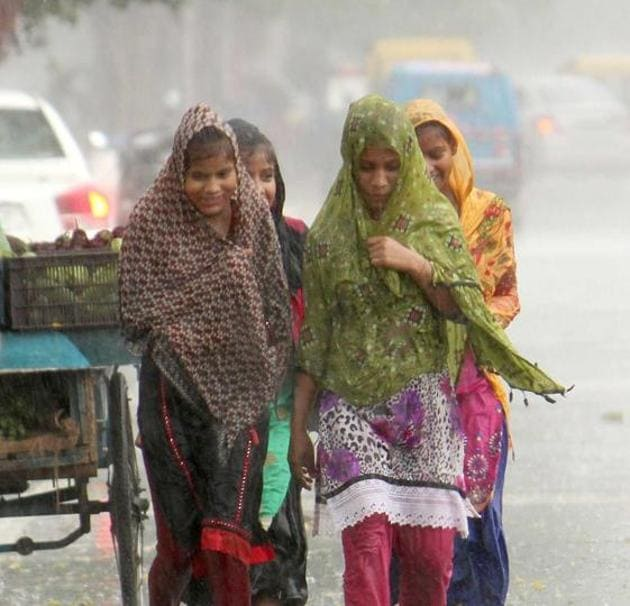 Girls making their way through the rain in Mohali on Friday. Wind up to 55 km per hour blew along with the rain.(Gurminder Singh/HT)