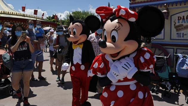 The iconic cartoon characters Minnie and Mickey Mouse walk with the visitors at the Hong Kong Disneyland on Thursday, June 18, 2020.(AP)