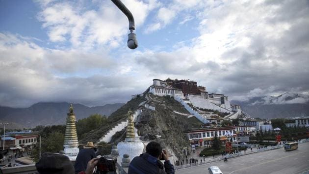 Tourists take photos of the Potala Palace beneath a security camera in Lhasa, Tibet. The railway project is part of the 435-km railway project linking Lhasa and Nyingchi, also known as Linzhi, in southwest China's Tibet Autonomous Region (TAR).(AP)