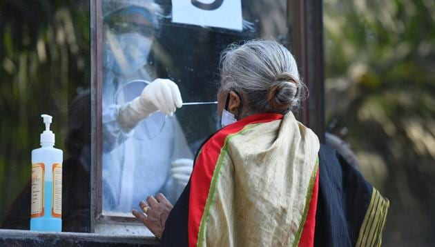 A medical professional collects a swab sample from a woman to test for COVID-19 infection at Swami Parmanand Prakritik Chikitsalaya Yoga & Anusandhan Kendra in West Vinod Nagar, New Delhi.(Raj K Raj/HT PHOTO)