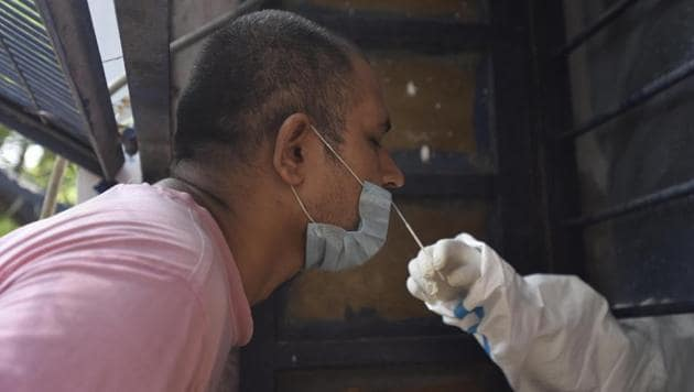 A medic collects swab sample from a man to test for Covid-19 infection at Gandhi Nagar in New Delhi on Sunday.(Sonu Mehta/HT PHOTO)