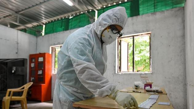A health worker in PPE prepares COVID-19 Ag rapid antigen test kits at a tesing centre in SKV Government Girls Senior Secondary School, in Chandni Chowk, New Delhi.(Amal KS/HT PHOTO)