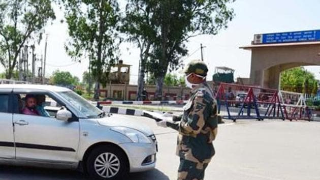BSF personnel note down details of cars ferrying Pakistani nationals who had been stuck in India after the Covid-19 lockdown before they enter the Integrated Check Post (ICP) to cross over from the Attari-Wagah border in Attari, Punjab.(HT Photo)