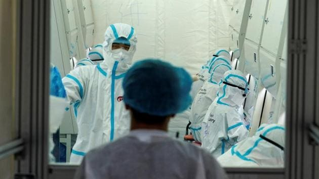 Staff members in protective suits work inside a mobile laboratory for nucleic acid testing, at a sports centre in Daxing district following a new outbreak of the coronavirus disease (COVID-19) in Beijing, China June 23, 2020.(REUTERS)
