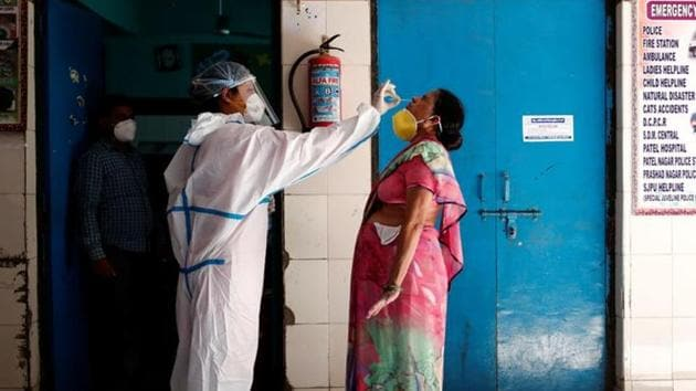 A medical worker collects a sample from a woman at a school turned into a centre to conduct tests for the coronavirus disease (COVID-19), amidst its spread in New Delhi.(REUTERS)