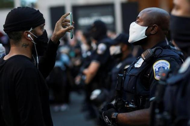 A demonstrator holds a mobile phone as he faces police officers near Black Lives Matter Plaza as racial inequality protests continue, Washington, June 23, 2020(REUTERS)