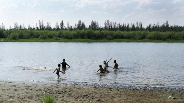In this handout photo taken Sunday, June 21, 2020 and provided by Olga Burtseva, children play in the Krugloe lake outside Verkhoyansk, the Sakha Republic, about 4660 kilometers (2900 miles) northeast of Moscow, Russia.(AP)