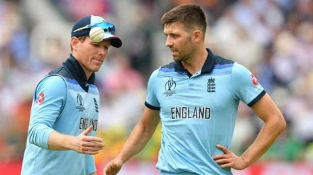 England's captain Eoin Morgan (L) speaks with teammate England's Mark Wood(AFP)