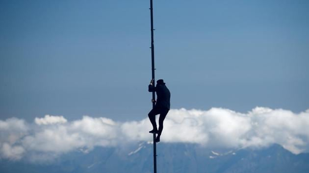 Swiss acrobat Ramon Kathriner performs on a pole during the Airshow, marking the reopening of facilities after the coronavirus disease (COVID-19) lockdown in Les Diablerets, Switzerland, June 23, 2020. (REUTERS/Denis Balibouse)