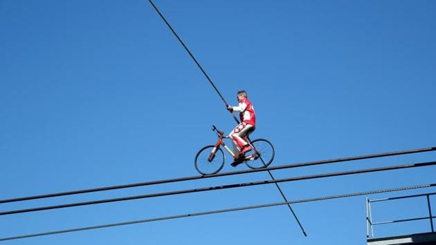 Swiss acrobat Freddy Nock balances on a bicycle on the cable of the Glacier 3000 cable car during the Airshow, marking the reopening of facilities after the coronavirus disease (COVID-19) lockdown in Les Diablerets, Switzerland, June 23, 2020. (REUTERS/Denis Balibouse)