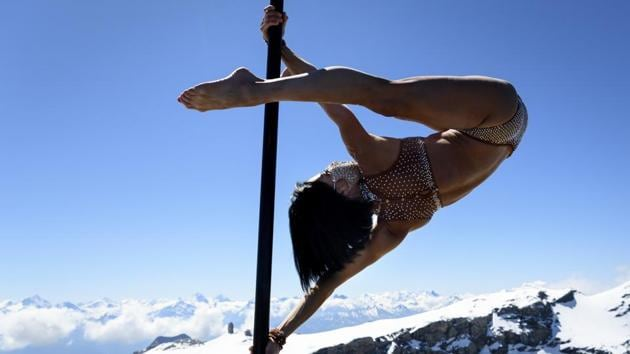 Pole acrobatic artist Sheila Nicolodi performs on a pole dance on the top of the mountain 3000 meters above sea level with Swiss Alps in the background during the Glacier 3000 Air Show to draw attention to the dramatic situation in the event industry due to the coronavirus outbreak in the village Les Diablerets of the municipality Ormont-Dessus, Switzerland, Tuesday, June 23, 2020. (Laurent Gillieron/Keystone via AP)