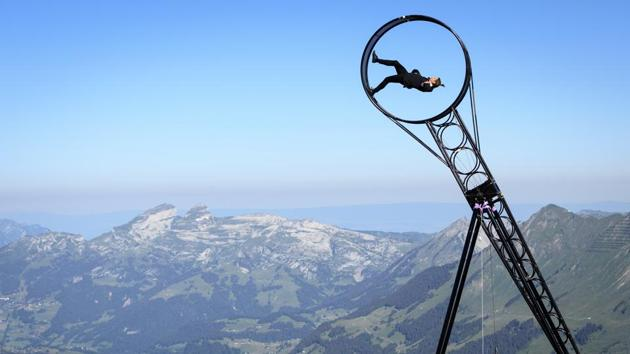 Switzerland's and Australian acrobatic artist Ramon Kathriner performs on a 'Wheel of Death' with Swiss Alps in the background during the Glacier 3000 Air Show to draw attention to the dramatic situation in the event industry due to the coronavirus outbreak in the village Les Diablerets of the municipality Ormont-Dessus, Switzerland, Tuesday, June 23, 2020. (Laurent Gillieron/Keystone via AP)
