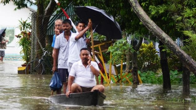 People move to safer place in a boat after floodwater enters the town in Assam's Dibrugarh on Thursday(ANI Photo)