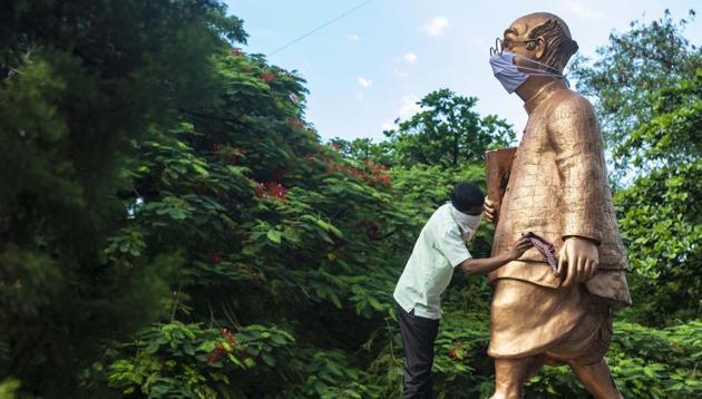 """A worker cleans the statue of """"Common Man"""" –wearing a facemask, at Symbiosis Vishwabhavan campus, in Pune.(Pratham Gokhale/HT Photo)"""
