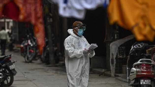 A health worker in PPE conducts a door to door screening survey for coronavirus in Karol Bagh's Ragarpura area, in New Delhi.(Biplov Bhuyan/HT PHOTO)