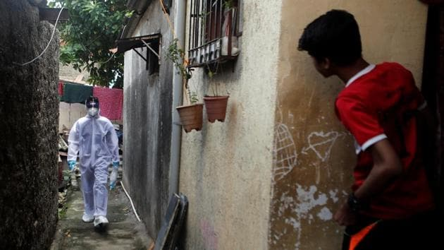 A healthcare worker wearing personal protective equipment (PPE) walks in an alley of a slum area during a check-up camp for the coronavirus disease (Covid-19) in Mumbai.(REUTERS)