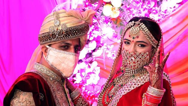 Rajasthan, June 25 (ANI): Bride and groom wear masks pose for photographs during their wedding ceremony, in Tonk on Thursday. (ANI Photo)(ANI)