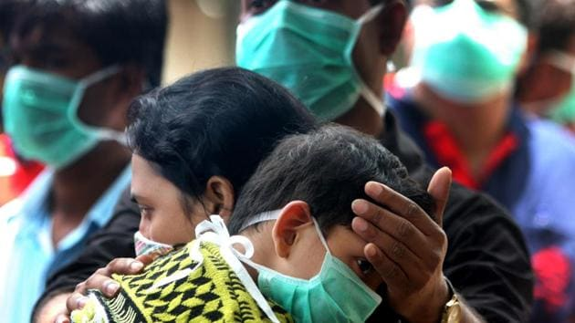 A family wait to be tested for the A(H1N1) virus - swine flu - outside Naidu Hospital in Pune.(HT photo)