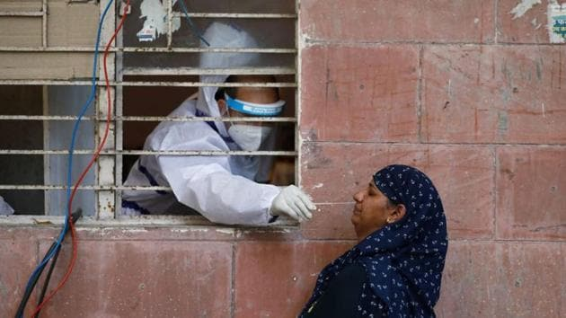A medical worker collects a sample from a woman at a centre to conduct tests for the coronavirus disease (Covid-19) amidst its spread in New Delhi on June 25, 2020.(Reuters Photo)