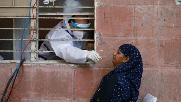 A medical worker collects a sample from a woman at a centre to conduct tests for the coronavirus disease (COVID-19), amidst its spread in New Delhi, India June 25, 2020.(REUTERS)