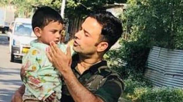 A policeman in Jammu and Kashmir is seen carrying a boy to safety in Sopore on Wednesday.(Twitter/@KashmirPolice)
