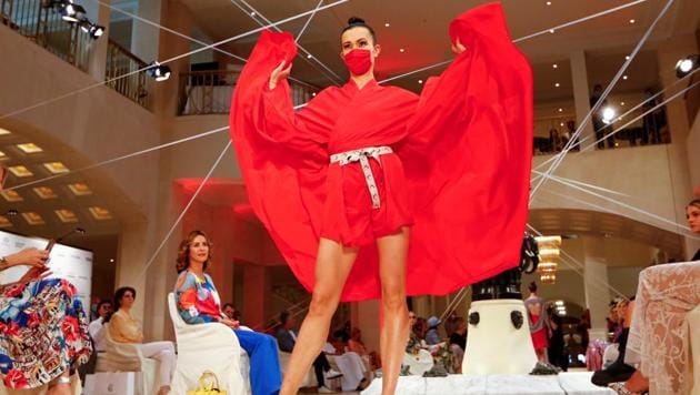 A model wears a face mask as she presents creations of the 2021 summer collection by designer Anja Gockel at Adlon Hotel, following the coronavirus disease (COVID-19) outbreak in Berlin, Germany, June 30, 2020.(REUTERS)