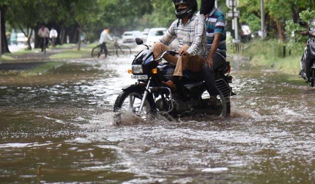 Two wheeler riders struggle to get through a waterlogged spot in Sector 9 after a heavy spell of rain in June this year.(HT Photo)
