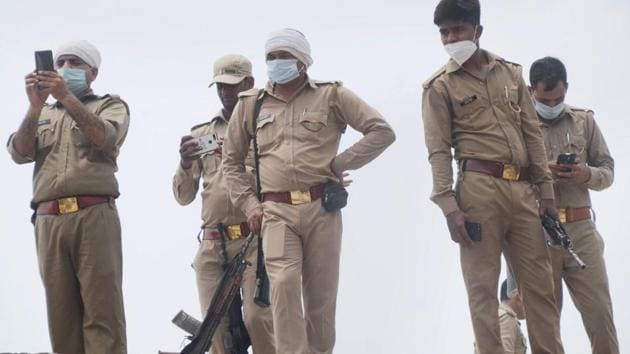 Police personnel at the residence of criminal Vikas Dubey, after an encounter in Bikaru village where 8 police personnel lost their lives, in Kanpur on July 4.(PTI)