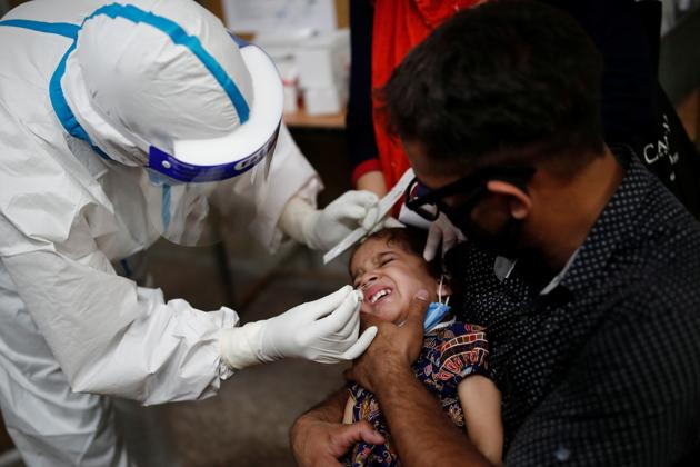 A health worker in personal protective equipment (PPE) collects a sample using a swab from a girl at a local health centre to conduct tests for the coronavirus disease (Covid-19), amid the spread of the disease, in New Delhi.(REUTERS)