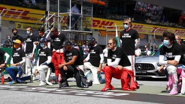 Mercedes' Lewis Hamilton, Ferrari's Sebastian Vettel and the rest of the drivers kneel on the grid.(REUTERS)