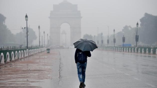 A pedestrian is seen holding an umbrella during rain, near India Gate, Rajpath, in New Delhi in January 2020.(Arvind Yadav/HT File Photo)