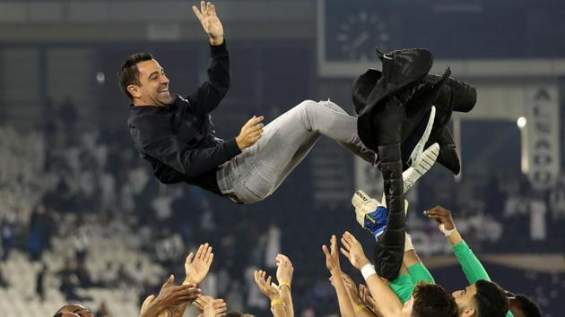 (FILES) In this file photo taken on January 17, 2020, Al-Sadd's Spanish coach Xavi is thrown into the air by his players as they celebrate winning the final match of the Qatar Cup against Al-Duhail at the Jassim Bin Hamad Stadium.(AFP)