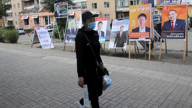 A resident carries groceries past posters and stands in the Songinokhairkhan district on the outskirts of Ulaanbaatar, Mongolia.(AP)