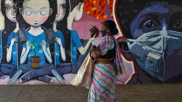 A woman wearing a protective mask walks past a graffiti during an extended nationwide lockdown to slow the spreading of coronavirus disease (COVID-19) in Mumbai.(REUTERS)
