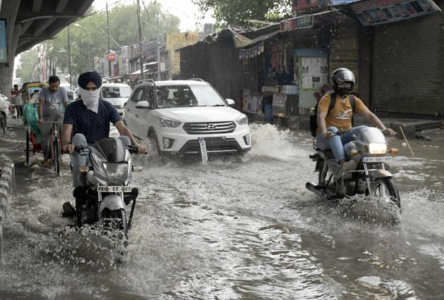 Commuters wading through the waterlogged road near Clock Tower chowk in Ludhiana on Wednesday.(Harsimar Pal SIngh/HT)