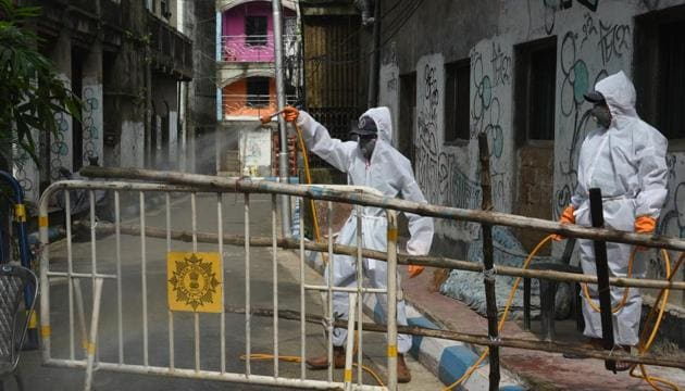Kolkata Municipal Corporation (KMC) workers wearing PPE coveralls chemically disinfect the Telenga Bagan area in Ultadanga -- one of the new coronavirus containment zone in Kolkata, West Bengal, India, on Thursday, July 09, 2020.(Photo: Samir Jana/Hindustan Times)