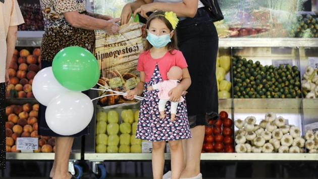 FILE- A child wearing a face mask clutches a doll at a food market in Bucharest, Romania, Wednesday, July 1, 2020.(AP)