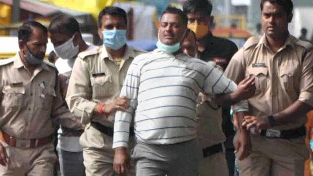 Gangster Vikas Dubey, the main accused in killing of eight policemen in the Kanpur encounter recently, being apprehended by police personnel after a nearly week-long manhunt, in Ujjain on Thursday.(PTI Photo)