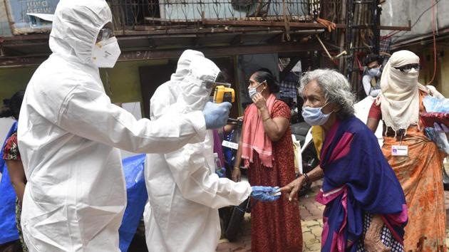 Health care staff check the temperature and pulse rate of the residents of Dharavi during Covid-19 pandemic.(Satyabrata Tripathy/HT Photo)