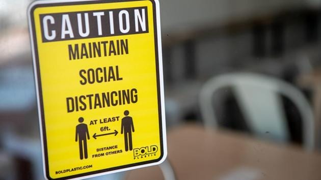 A social distancing sign is displayed in the window of a business. (Representational image)(Bloomberg)