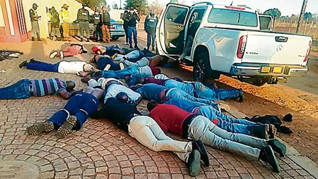 A photo released by police shows suspects lying on the ground at the site of the hostage incident in Johannesburg.