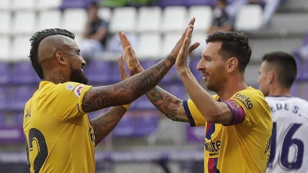Barcelona's Arturo Vidal, left, celebrates with his teammate Lionel Messi after scoring his side's first goal during the Spanish La Liga soccer match between Valladolid and FC Barcelona at the Jose Zorrilla stadium in Valladolid, Spain, Saturday, July 11, 2020. (AP Photo/Manu Fernandez)(AP)