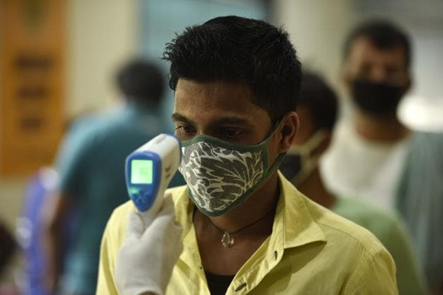 A health worker uses an infrared thermometer thermal screen a man during swab sample collection for coronavirus testing at Sukhrali Enclave near Shiv temple, in Gurugram on Sunday.(Parveen Kumar/HT File Photo)