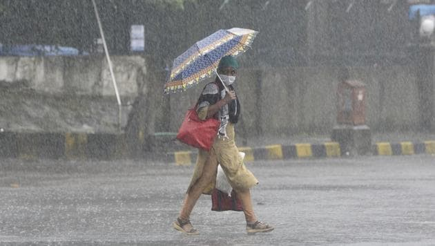 Woman walks during heavy rain at Andheri(E) in Mumbai on Sunday.(Satyabrata Tripathy/HT Photo)