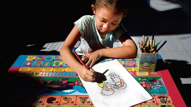 A girl colours a sketch made to educate children on Covid-19 in Bangkok, Thailand.(AP Photo)