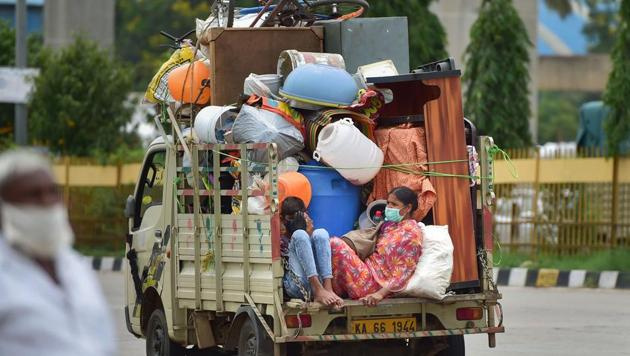 Migrants with their belongings travel in a tempo as they leave the city after authorities announced one week lockdown due to surge in Covid-19 cases in Bengaluru on Monday.(PTI Photo)
