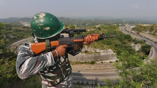 A CRPF jawan keeps a watch on the Jammu-Srinagar national highway ahead of the Amarnath Yatra on Tuesday.(PTI)