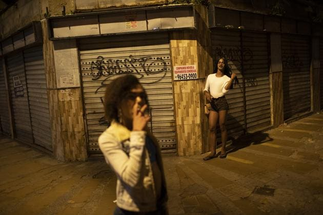 """Transgender sex worker Alice Larubia smokes a cigarette as she waits for customers in Niteroi, Brazil, Saturday, June 27, 2020, amid the new coronavirus pandemic. After a month quarantining at home with some financial support from family, Larubia resumed work in Niteroi, a city across the bay from Rio. """"Necessity spoke louder (than the pandemic) and I had to come back to the street,"""" Larubia said while waiting for clients with a small group of colleagues.(AP)"""